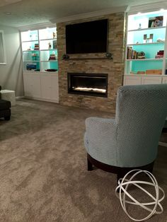 Contemporary gas fireplace, Desert Quartz ledge stone, gray, white, Tiffany blue, custom built in cabinets, family room, embroidery hoop orb