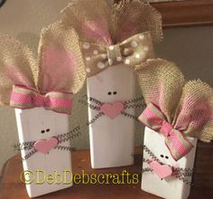 How adorable would these cute wooden Easter bunnies look with the rest of your spring decorations! Display these on your mantle, table or as part of a centerpiece! Each bunny has burlap ears with a ribbon bow, black wire whiskers and a pink heart nose! Set of 3.  Each bunny is made from 2x4 wood with heights of 8, 10 and 12 (not including ears). Insides of ears have been painted a light pink. Each wood block has been sanded, painted, lightly distressed then sealed with a protective coating…