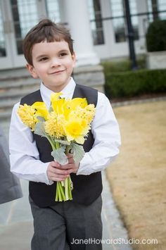 This cute little ring bearer is carrying the bridesmaids bouquet consisting of Hyacinth and daffodils