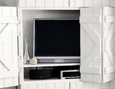 Hiding TVs behind hinged and sliding doors or wall decorative panels is one of interior design trends and modern ideas for home staging