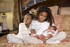 Ten and four year old African American sisters holding their newborn sibling Stock Photo - 6334233