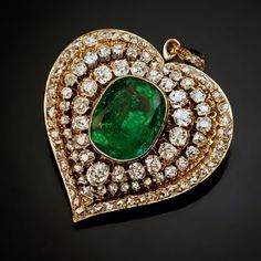 romanov_russia: an antique Victorian heart-shaped pendant centered with an emerald surrounded by six carats of old mine cut more