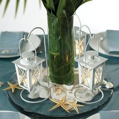 $7.43-$9.30 for a set of two. Center piece idea. Surrounded by moss and flowers. One for each table? at differing heights provided by wood....  Mini White Hanging Lantern Tea Light Holders by Beau-coup