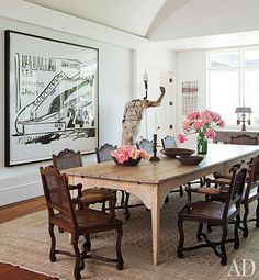 Antique French cane chairs surround a 17th-century farm table in the dining room; the work on paper is by Warhol.