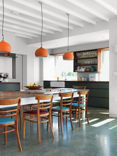 Above the dining room's Hodgson & Barker Antiques table—found on eBay—are ceramic pendant lights from Hand & Eye Studio. The architect acquired the wood chairs secondhand.