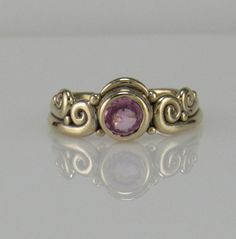 R1059- 14k Yellow Gold Ring with 5.5 mm Pink Sapphire. The top of the ring measures 8 mm Wide and the band is 2 mm wide. It is a size 7.5 and can be sized down for Free. Small fee for sizing up, please contact me with your exact size and I will let you know the cost.  All of my rings are made using the Lost Wax Method of casting and are one of a kind. To learn more about the process and Me please visit my website at: www.denimanddiamondsjewelry.com  Thanks for looking and feel free to…