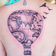 This gorgeous hot air balloon tattoo is detailed with many different travel symbols. The compass, map, birds, and suitcase all come together to make this an amazing piece of art.