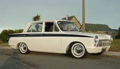 De Ford Cortina, met de groene streep aan de zijkant word hij een Lotus Cortina genoemd, dit is de sporteditie met een sportonderstel en was een klein stukje verlaagd. het is de eerste sportsaloon van Lotus, was bijna volledig gemaakt van aluminium en had allerlei snufjes die wij ook in een auto hebben tegenwoordig zoals stuurbekrachtiging, een '5-speed' versnellingsbak met een achteruit en airco. Het is ontworpen door Ford in Amerika en herontworpen door Lotus in Engeland en kwam op de…