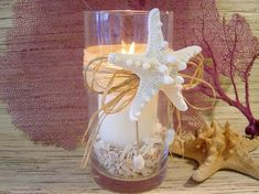 centerpiece with white knobby starfish, shells, candle, glass vase & raffia