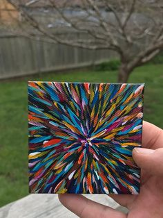 This piece is one of a collection of abstract starburst works. The mini canvas has many layers of paint with a tiny crystal in the center to radiate light and color.