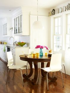 white kitchen brown wood round dining table white modern chairs