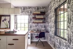 Wallpapered home office with open shelves and dark wood desk