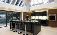 High gloss Black and timber kitchen under a large glass conservatory #kitchens #conservatory