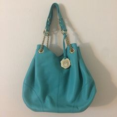 "NWOT Vince Camuto Turquoise Leather Bag Authentic NWOT Vince Camuto spacious shoulder bag in a stunning vibrant bluish turquoise color. 100% genuine leather. Pristine condition❗️This bag has never been used. The pictures show that the shiny gold hardware, straps, interior vinyl and leather are in perfect condition. Comes with accessory card. Snap enclosure at the top, one zippered pocket, one cell phone pocket, a pen pocket and a wall pocket. Dimensions: 13"" H x 18.5"" W x 10"" strap drop…"