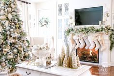 Gold and silver decorated, white flocked elegant Christmas tree. Christmas mantel with white ruffled stockings