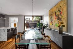 Colorful wall art adds style and elegance to the neutral dining space and kitchen