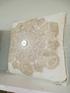 """This 14"""" square pillow is trimmed in a cream quilted fabric. An old doily & button are centered on the pillow with a contrast piping on the edges."""