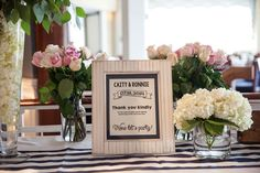 framed gift table sign in front of rose and hydrangea arrangements