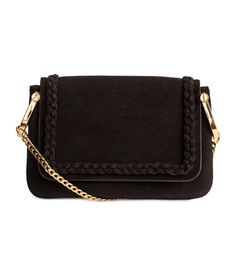Black. Small shoulder bag in imitation leather with surface in  regenerated leather. Flap with decorative braided trim and magnetic fastener, metal chain