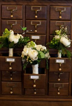 Wedding bouquets in a vintage card catalog for a library themed wedding.