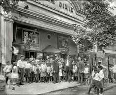 """Washington, D.C., 1920. """"Dixie Theater crowd, H Street."""" Now playing: """"Hidden Dangers"""" (Episode 2, """"The Murder Mood""""), """"The Primal Lure"""" and """"When Cowboy Was King."""" Kids get in for 11 cents! Next door: People's Drug Store No. 5. National Photo Company Collection glass negative."""