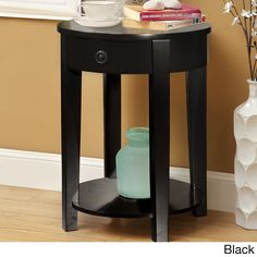This stylish and modern occasional table is constructed of solid wood and designed with single and open shelf storage. The elegant, round structure is coated with your choice of black or white finish.