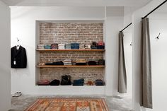 built-in shelves against a brick wall & traditional rug on a concrete floor. Like the juxtaposition.