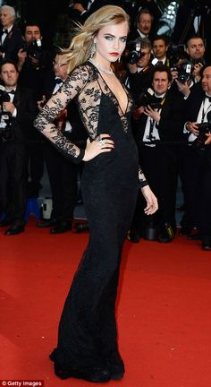 Cara strutted her stuff in the black lace gown with a plunging neckline while she finished her look with smokey eyes and dark red lips