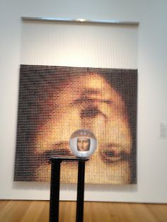 Upside down Mona Lisa created with spools of thread. Yes, I said spools of thread! Looking through prism turns image right side up. Huh?