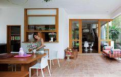 Este terraço é integrado à cozinha pela janela guilhotina e à sala de jantar (à dir.) pelos painéis deslizantes com vidro. Projeto assinado pelo arquiteto Jorge Siemsen