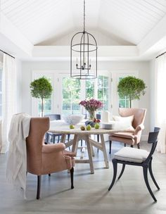 A breakfast nook off the kitchen has become a light-filled gathering space for friends and family. The table is by Bobo Intriguing Objects, and the dining chairs are by RH, with custom-made cushions in a Clarence House fabric. The wingback chairs, which were sourced from eBay, are upholstered in Holly Hunt leather, and the curtains are of a Lee Jofa fabric.