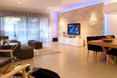 תמונה - סלון, סלון בסגנון מודרני המשלב קיר בריקים לטלוויזיה ומשחקי תאורה בעיצוב ענבל ברקוביץ' - Adira.co.il