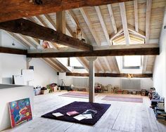I would love a space like this. Great exposed beams with a punch of colour adding to the flavor of this loft.