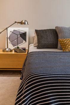 O painel de madeira camufla o guarda-roupas e combina com as soluções de marcenaria feitas sob medida para o local. Ampla, a bancada em frente a cama serve de aparador de televisão e como escritório para o home office.