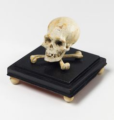 A South German miniature carved wood skull and crossbones. Painted white and mounted to an ebonised wooden plinth on bone feet. Minor paint losses. 17th / 18th C.