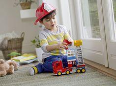 Knabe spielt mit LEGO DUPLO Feuerwehr Löschfahrzeug
