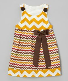 Warm, earthy colors light up this pretty little frock. With a cheerful zigzag pattern and bow at the waist, it's a sure favorite for family get-togethers and special events. The soft cotton construction stays comfy, while buttons on the shoulders make changing easy as pie.