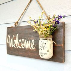 Hand painted Welcome real wood sign. Includes rope for hanging and the Mason jar (flowers not included). I can do any color combo upon request. Size