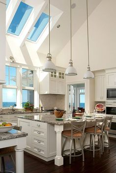 White kitchen cabinets, dark wood floors, vaulted ceilings with skylights, granite countertops, large kitchen island