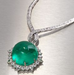 An emerald and diamond pendant necklace  centering a round cabochon emerald, weighing 96.92 carats, within a pear and round brilliant-cut diamond surround, suspended from a detachable necklace set with tapered-baguette-cut diamond three-stone sections; estimated total diamond weight: 9.85 carats; mounted in eighteen karat white gold; diameter: 1 1/2in.