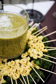 Tortellini skewers with pesto dipping sauce. Great idea for an outdoor party.