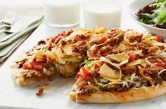 Taco Pizza. Easy to make and delicious!  Buy refridgerated pizza dough. Bake dough until almost done - dough should still be soft - about 10 minutes. Take out of oven - spread with sour cream, add cooked hamburg, salsa and cheese.  Put back in oven for about 10 minutes or until  cheese is melted. Remove and add lettuce, tomatoes, olives and top with more cheese. Serve!!