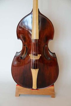 """Luthier: Christian Laborie - A four-string double bass in a gamba shape with a flat back, gut strings and viola da gamba """"C"""" holes. The fingerboard and tailpiece are made of plain figured maple. The tuning adjusters are of ebony or boxwood. This instrument is convenient for continuo playing in Baroque or Classical performance practice ensembles. String length: 41'' (104cm) Total length: 5' 11'' (180cm) Top length: 43'' (109cm)"""