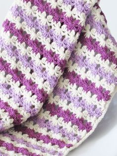 Do you love easy and quick crochet blanket patterns? Then try this beautiful afghan that is made with a simple stitch that looks like rows of flowers. This free pattern is beginner friendly and will help you make a unique afghan fast. #crochetblanket, #crochetafghan, #crochet, #freecrochetpattern, #crochetbabyblanket
