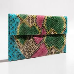 Green pink blue python clutch by Verinosa Add a dash of creativity to your outfit with this cheerful multi coloured clutch. An eclectic melting pot of inspiring handmade artful patterns applied on authentic python. The perfect clutch for a unique fabulous eye catching look.Designer Colour: Green Pink BlueGenuine Python snakeskin: IndonesiaInterior: Suede lining and debossed designer letteringMagnetic-fastening front flapAvailable with and without removable chain strapDimensions: 26.5cm x…