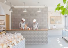 Fresh loaves and sugary treats are presented alongside wooden surfaces, ceramic tiles and plants at this renovated bakery in Kiryu, Japan