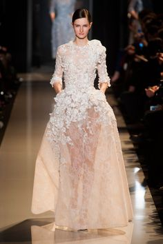 Elie Saab.  This is too much sheer, way too much leg and too much naked for a wedding gown.  You can practically see the babymaker!  And If I'm paying thousands fo dollars for a wedding gown, damnit, I want petticoats, slips, corset, and bra built in and included in the price without paying extra for something that belongs in the gown in the first place.  No one could wear this in front of a priest or minister without everybody blushing!