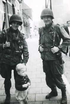 US soldiers stand with a little boy in Veghel, Netherlands - September 1944  The man on the right was later identified, 62 years after the photo was taken by veterans visiting Eindhoven, as 1LT Herbert Viertel, B Company, 1st BN, 506 PIR, 101st Airborne Division.