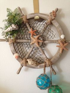 Improved upon the original tutorial, this time with pre-made ship wheel.This tutorial will instruct in how to build the ship wheel, and decorate it with nautical. Seashell Wreath, Seashell Crafts, Beach Crafts, Home Crafts, Diy Crafts, Deco Marine, Glass Floats, Pine Cone Crafts, Nautical Theme