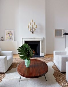 In a New York townhouse by D'Apostrophe Design, a Jean Royère light fixture is mounted above the library's fireplace, which is flanked by a Picasso drawing and a Roy Lichtenstein painting; the Jean-Michel Frank club chairs are by Hermès, the cocktail table is a vintage piece by Prouvé and Charlotte Perriand, and the glass vase is by Thaddeus Wolfe   archdigest.com